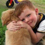 Niño abrazado con su perro en el jardín